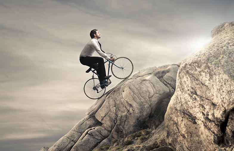 man riding bicycle up a rocky hill